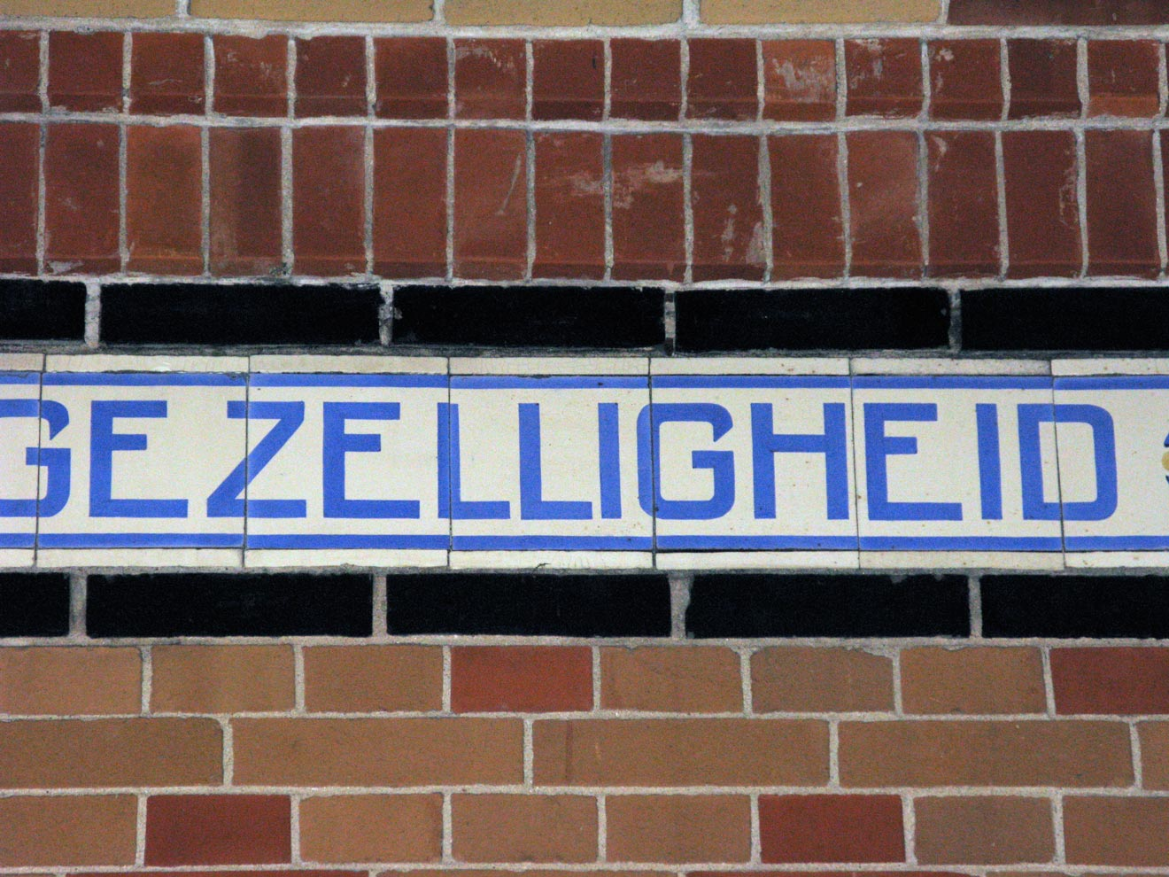 The lettering on the frieze is not constrained to the rhythm of the tiles but is spaced in a much more sophisticated manner.