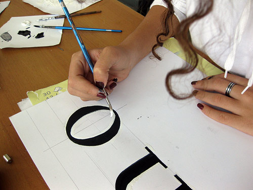 Nora Ali drawing type using black and white gouache paint, at the Bruno Maag   Dalton Maag Type Design workshop at the German University in Cairo.